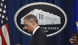 Attorney General Eric Holder steps away from the podium at a news conference at the Department of Justice on Tuesday, Feb. 3, 2015 in Washington. (AP Photo/Kevin Wolf)