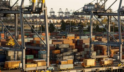 In this Wednesday, Jan. 14, 2015, file photo, shipping containers are stacked up waiting for truck transport at the Port of Los Angeles. (AP Photo/Damian Dovarganes)