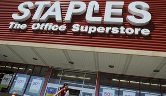 FILE - In this May 26, 2009 file photo, a woman walks past a Staples office supply store in Danvers, Mass. Staples on Wednesday, Feb. 4, 2015 announced it is buying Office Depot in a cash-and-stock deal valued at nearly $6 billion. (AP Photo/Lisa Poole, File)