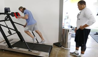 ADVANCED FOR USE SUNDAY FEB 8 AND THEREAFTER David Vobora owner of Performance Vault shows James Castleman how to tweak his running technique during a workout at Performance Vault in Dallas, on Friday, Jan. 23, 2015. Castleman is a defensive lineman at Oklahoma State University and NFL prospect. (AP Photo/The Dallas Morning News, Vernon Bryant) MANDATORY CREDIT, NO SALES, MAGS OUT, TV OUT, INTERNET USE BY AP MEMBERS ONLY