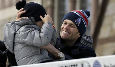 New England Patriots quarterback Tom Brady, right, helps his son Benjamin with his coat and hat during a parade in Boston Wednesday, Feb. 4, 2015, to honor the Patriots' victory over the Seattle Seahawks in Super Bowl XLIX Sunday in Glendale, Ariz. (AP Photo/Steven Senne)