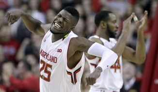 Maryland forward Jonathan Graham, front, and guard/forward Dez Wells react after Penn State was forced to turn over the ball on a five second violation in the second half of an NCAA college basketball game, Wednesday, Feb. 4, 2015, in College Park, Md. Maryland won 64-58. (AP Photo/Patrick Semansky)