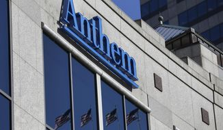 The Anthem logo hangs at the health insurer's corporate headquarters in Indianapolis, Thursday, Feb. 5, 2015. Hackers broke into the company's database storing information for about 80 million people in an attack bound to stoke fears many Americans have about the privacy of their most sensitive information. (AP Photo/Michael Conroy)
