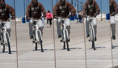 In this June 7, 2012 photo, a bicyclist is reflected in the exterior mirrored panels of Revel, the newest casino in Atlantic City N.J. (AP Photo/Wayne Parry)