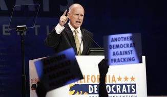 California Gov. Jerry Brown speaks as protesters opposing fracking hold up signs during the general session at the California Democrats State Convention in Los Angeles on March 8, 2014. (Associated Press) **FILE**