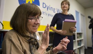 Linda Jarrett, left, applauds Wanda Morris, right, CEO of Dying with Dignity, as she speaks to the media group's offices in Toronto. Friday, Feb. 6, 2015.  Canada's highest court Friday, unanimously struck down a ban on doctor-assisted suicide for mentally competent patients with terminal illnesses. (AP Photo/The Canadian Press)