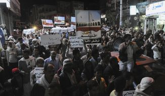 """Yemeni people hold a rally to protest against Shiite rebels' announcement of taking over the country in Taiz, Yemen, Friday, Feb. 6, 2015. Yemen's powerful Shiite rebels announced on Friday that they have taken over the country and dissolved parliament, a dramatic move that finalizes their monthslong power grab. Arabic writing on banners that reads, """"We reject the coup."""" (AP Photo/Anees Mahyoub)"""