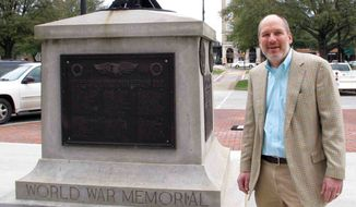 In this Jan. 22, 2015, photo, Greenwood Mayor Welborn Adams stands beside the Greenwood County memorial in Greenwood, S.C., that honors its citizens who died in recent wars. The World War I and World War II soldiers are separated into colored and white. Adams raised $15,000 to put new plaques on the statue, but a state law won't allow him to put them up. (AP Photo/Jeffrey Collins)