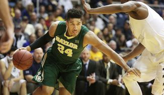 Baylor guard/forward Ishmail Wainright (24) drives past West Virginia forward Jonathan Holton, right, during the first half of an NCAA college basketball game, Saturday, Feb. 7, 2015, in Morgantown, W.Va. (AP Photo/Raymond Thompson)