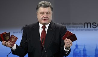 Ukraine's President Petro Poroshenko holds Russian passports  claiming they are  proof of  the presence of Russian troops in Ukraine as he addresses the 51. Security Conference in Munich, Germany, Saturday, Feb. 7, 2015. The conference on security policy takes place from Feb. 6, 2015 until Feb. 8, 2015. (AP Photo/Stringer)