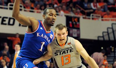 Oklahoma State guard Phil Forte (13) drives past Kansas guard Wayne Selfen Jr. during the first half of an NCAA basketball game in Stillwater, Okla., Saturday, Feb. 7, 2015. (AP Photo/Brody Schmidt)
