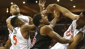 Virginia's Justin Anderson, right, Darion Atkins (5) and Isaiah Wilkins, top left, combine to block a shot by Louisville's Wayne Blackshear, second from right, during first-half NCAA college basketball game action Saturday, Feb. 7, 2015, in Charlottesville, Va. (AP Photo/The RichmondTimes-Dispatch, Joe Mahoney)