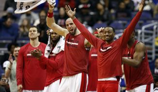 Washington Wizards guard John Wall, right, and center Marcin Gortat (4), from Poland, second from right, and others cheer from the bench late in second first half of an NBA basketball game against the Brooklyn Nets, Saturday, Feb. 7, 2015, in Washington. The Wizards won 114-77. (AP Photo/Alex Brandon)