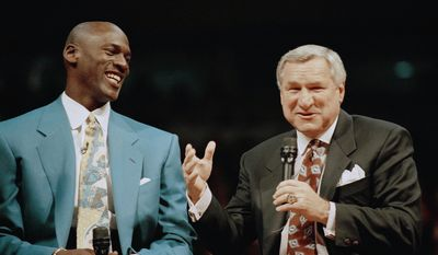 """FILE - In a Nov. 1, 1994 file photo, former Chicago Bulls great Michael Jordan shares a moment with Dean Smith, his former coach at North Carolina, during ceremonies honoring Jordan at Chicago's United Center.  Smith, the North Carolina basketball coaching great who won two national championships, died """"peacefully"""" at his home Saturday night, Feb. 7, 2015, the school said in a statement Sunday from Smith's family. He was 83. (AP Photo/Pool, File)"""