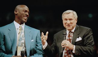 "FILE - In a Nov. 1, 1994 file photo, former Chicago Bulls great Michael Jordan shares a moment with Dean Smith, his former coach at North Carolina, during ceremonies honoring Jordan at Chicago's United Center.  Smith, the North Carolina basketball coaching great who won two national championships, died ""peacefully"" at his home Saturday night, Feb. 7, 2015, the school said in a statement Sunday from Smith's family. He was 83. (AP Photo/Pool, File)"