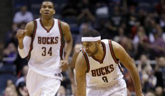 Milwaukee Bucks' Giannis Antetokounmpo (34) watches as teammate Jared Dudley reacts after Dudley's three-point shot during the first half of an NBA basketball game against the Brooklyn Nets Monday, Feb. 9, 2015, in Milwaukee. (AP Photo/Morry Gash)