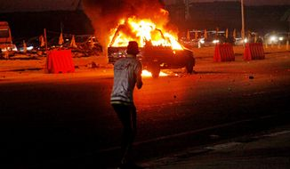 An Egyptian looks at a vehicle lit on fire during a riot outside the Air Defense Stadium in a suburb east of Cairo, Egypt, in this Sunday, Feb. 8, 2015, photo. Egypt's Cabinet has indefinitely suspended the national soccer league after more than 20 fans were killed in a stampede and clashes with police outside the Cairo stadium. (AP Photo/Ahmed Abd El-Gwad, El Shorouk Newspaper)