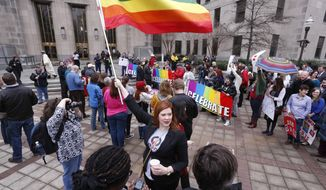 Amanda Keller holds a flag as she joins other gay marriage supporters in Linn Park, at the Jefferson County courthouse, Monday, Feb. 9, 2015, in Birmingham, Ala. Alabama began issuing marriage licenses to same-sex couples Monday after the U.S. Supreme Court refused to stop the marriages from beginning in the conservative southern state. (AP Photo/Hal Yeager)