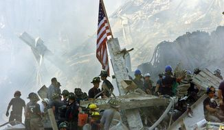 An American flag flies over the rubble of the collapsed World Trade Center buildings in New York on Sept. 13, 2001. (Associated Press) **FILE**