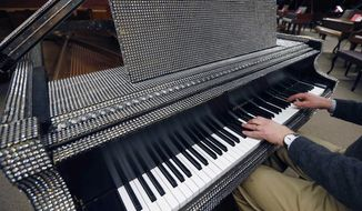 In this Saturday, Jan. 24, 2015 photo, Tim Howard, of Boston, plays a piano once owned by Liberace at the Piano Mill in Rockland, Mass. A section of roof collapsed into the music store's showroom under the weight of snow Tuesday, Feb. 10, 2015, after Rockland received 29 inches of new snow the previous day. Store owner Rob Norris said it is unclear if the Liberace piano was damaged. No one was in the building at the time of the collapse, nor is anyone being allowed inside until a structural engineer assesses damage. (AP Photo/Michael Dwyer)