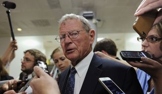 "FILE - in this July 8, 2014, file photo, Sen. James Inhofe, R-Okla., speaks to reporters on Capitol Hill in Washington. Inhofe, who will take over the Senate Environment and Public Works Committee in January, said in a statement late Tuesday, Nov. 25, 2104, that a stricter standard to be announced Wednesday by the Obama administration on smog-forming pollution allowed in the air ""will lower our nation's economic competitiveness and stifle job creation for decades."" He vowed ""vigorous oversight"" of the proposal in his new position. (AP Photo/Susan Walsh)"