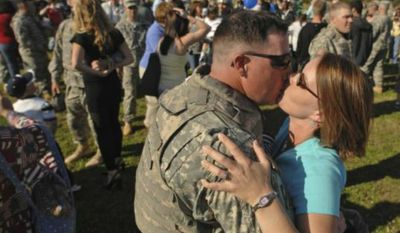 Staff Sergeant Steven Smith of the 1st Brigade Combat Team, 3d Infantry Division, is welcomed home by his wife Jackie at Fort Stewart in Georgia after a deployment. (Associated Press) ** FILE **