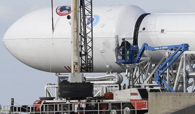 Maintenance is performed by workers on the Falcon 9 SpaceX rocket at launch complex 40 at the Cape Canaveral Air Force Station in Cape Canaveral, Fla., Monday, Feb. 9, 2015. The Sunday launch attempt was scrubbed and SpaceX will try again on Tuesday evening. (AP Photo/John Raoux)
