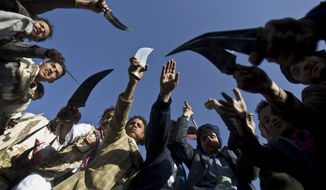 Supporters of Houthi Shiites wave traditional daggers and dance as they celebrate the fourth anniversary of the uprising in Sanaa, Yemen, Wednesday, Feb. 11, 2015. The United States, Britain and France moved to close their embassies in Yemen on Wednesday, increasing the isolation of Shiite rebels who have seized power. (AP Photo/Hani Mohammed)