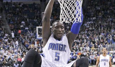 FILE - In this Jan. 16, 2015, file photo, Orlando Magic's Victor Oladipo (5) hangs on the rim after dunking the ball against the Memphis Grizzlies during the second half of an NBA basketball game in Orlando, Fla. Oladipo says he is donating a portion of his earnings from the Slam Dunk Contest during All-Star Weekend to three different hospitals earmarked for cancer treatment and research.  (AP Photo/John Raoux, File)