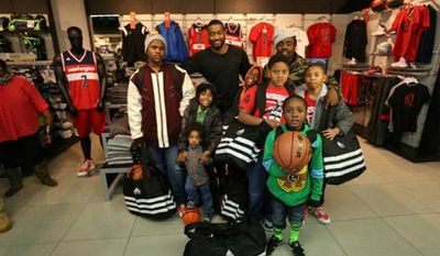 The Wizards' John Wall poses with the  group of area youth he recently took for a Christmastime shopping spree to the Adidas store in the District. (NBA Photos)