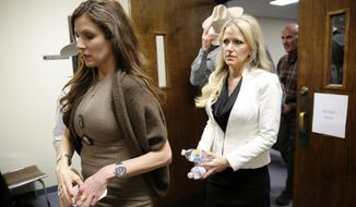 Taya Kyle, left, wife of slain Navy SEAL Chris Kyle, leaves the Erath County Donald R. Jones Justice Center courtroom following the days proceedings in Stephenville, Texas, during the capital murder trial of former Marine Cpl. Eddie Ray Routh, Wednesday, Feb. 11, 2015. Routh, of Lancaster, Texas, is charged with the 2013 deaths of Chris Kyle and his friend Chad Littlefield at a shooting range near Glen Rose, Texas. (AP Photo/The Dallas Morning News, Tom Fox, Pool)