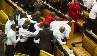 South African Economic Freedom Fighters, EFF,  disrupt the official opening session inside Parliament while security personnel dressed in white shirts try and stop the action in Cape Town, South Africa, Thursday, Feb. 12, 2015. Security guards entered South Africa's parliament on Thursday to remove opposition lawmakers who disrupted an annual address by President Jacob Zuma to demand that he answer questions about a spending scandal.   (AP Photo/Rodger Bosch, Pool)