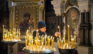 A women light candles in a church as she prays for  peace in eastern Ukraine in St. Volodymyr Cathedral in Kiev, Thursday, Feb. 12, 2015.   Leaders of Russia, Ukraine, France and Germany on Thursday emerged from marathon 16-hour talks to announce a comprehensive peace deal for eastern Ukraine, but questions remained whether Ukraine and the pro-Russian rebels have agreed on all of its terms.   (AP Photo/Efrem Lukatsky)