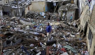 In this Tuesday, Nov. 25, 2014 photo, Mohammed al-Bakri, stands on the rubble of his family home in the Shati refugee camp in Gaza. The Aug. 4 airstrike killed six people, five of them relatives. Two of those killed were members of the militant group Islamic Jihad. Israel carried out scores of attacks on houses during its summer war with Gaza militants, alleging militants used them for military purposes. Palestinians say Israel's warplanes often struck without regard for civilians. (AP Photo/Adel Hana)