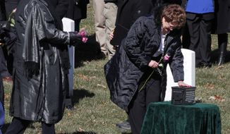 Cate Richards, mother of Marine Cpl. Robert Richards, touches his urn during his burial service at Arlington National Cemetery in Arlington, Va., Friday, Feb. 13, 2015. Richards, 28, of St. Petersburg, Fla., died Aug. 13, 2014. (AP Photo/Jacquelyn Martin)