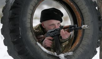 A newly mobilized Ukrainian soldier shows his skills during military drills in base Desna 100km north from Kiev, Ukraine, Friday, Feb. 13, 2015. Fierce fighting surged in East Ukraine as Russian-backed separatists mounted a major and sustained new push Friday to capture a strategic railway hub ahead of a weekend cease-fire deadline. (AP Photo/Efrem Lukatsky)