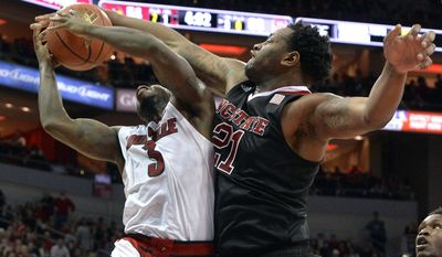 North Carolina State's BeeJay Anya, right, blocks the shot of Louisville's Chris Jones during the second half of an NCAA college basketball game, Saturday, Feb. 14, 2015, in Louisville, Ky. NC State won 74-65. (AP Photo/Timothy D. Easley)