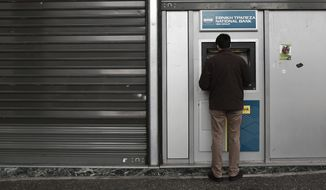 A man uses an ATM outside a National Bank branch in central Athens, Saturday, Feb. 14, 2015. This week the European Central Bank gave the green light for Greek banks to use another five billion Euro from the Emergency Liquidity Assistance mechanism in order to compensate for continuing deposit withdrawals. (AP Photo/Petros Giannakouris)
