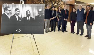 In this Feb. 5, 2015 photo, a group gathers at Congregation Mishkan Israel in Hamden, Conn., to remember when Dr. Martin Luther King, Jr., visited the temple to preach on Oct. 20, 1961. King is shown second from right in the 1961 photo with leaders of the temple at that time. (AP Photo/New Haven Register, Peter Hvizdak)