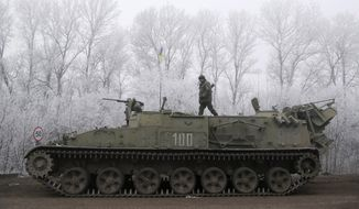 Ukrainian government soldier walks atop of his armored vehicle on the road between the towns of Dabeltseve and Artemivsk, Ukraine, Sunday, Feb. 15, 2015. (AP Photo/Petr David Josek)