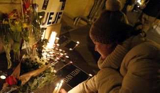 A woman lights a candle to pay respect to victims of the shooting attack in Copenhagen, at the Danish embassy in Paris, France, Sunday, Feb. 15, 2015. (AP Photo/Christophe Ena)