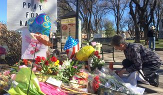 An unidentified woman kneels near a makeshift memorial for Kayla Mueller, Thursday, Feb. 12, 2015, in Prescott, Ariz. Mueller, a 26-year-old American woman held by Islamic State militants, was confirmed dead, her parents and the Obama administration said Tuesday. (AP Photo/Brian Skoloff)