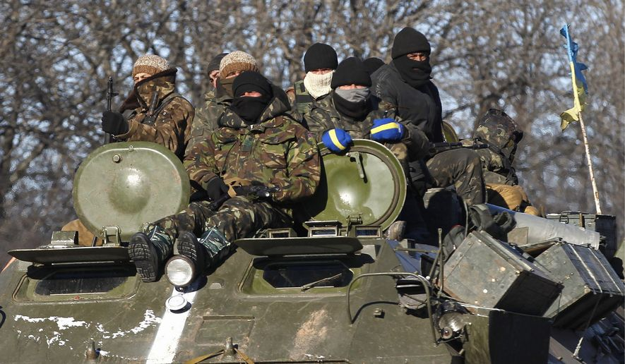 Ukrainian government soldiers sat on their armored vehicle driving on a road away from the town of Artemivsk as separatists pushed deeper into Debaltseve.