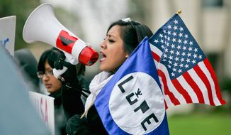 A woman chants in to her megaphone outside the federal courthouse in Brownsville, Texas, on Tuesday while protesting Judge Andrew Hanen's ruling that halted President Obama's amnesty order. (Associated Press)