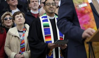 Rev. Michael Diaz, center, from Metropolitan Church in Houston, and other faith leaders and congregation members of various churches from around the state rally on the step of the Texas Capitol steps to call for more equality for same-sex couples, Tuesday, Feb. 17, 2015, in Austin, Texas. (AP Photo/Eric Gay)