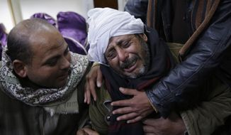 A man is comforted by others as he mourns over Egyptian Coptic Christians who were captured in Libya and killed by militants affiliated with the Islamic State group. (AP Photo/File)