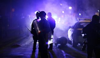 Police officers watch protesters as smoke fills the streets in Ferguson, Mo., after a grand jury's decision in the fatal shooting of Michael Brown, in this Nov. 25, 2014, file photo. (AP Photo/Charlie Riedel, File)
