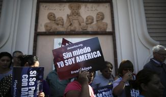 """A woman holds a sign that says in Spanish, """"without fear I am America,"""" during a rally in support of President Barack Obama's plan to protect more than 4 million people living illegally in the U.S. from deportation Tuesday, Feb. 17, 2015, in San Diego. Immigrants expressed disappointment Tuesday after a federal judge put a hold on the president's plan, but many said they haven't lost hope. (Associated Press) **FILE**"""