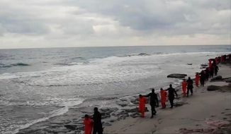 This file image made from a video released Sunday, Feb. 15, 2015, by militants in Libya claiming loyalty to the Islamic State group purportedly shows Egyptian Coptic Christians in orange jumpsuits being led along a beach, each accompanied by a masked militant. The Christians were beheaded. (AP Photo, File)