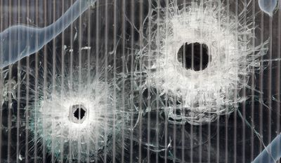 Bullet holes are seen in a window of a cultural club after an shooting attack in Copenhagen, Denmark, Tuesday, Feb. 17, 2015. A Danish gunman who attacked a free-speech seminar and a synagogue was released about two weeks ago from a jail where he may have been radicalized while serving time for a vicious stabbing. As Denmark mourned the two victims, these and other troubling details emerged Monday about Omar Abdel Hamid El-Hussein's path to the country's worst terror spree in three decades. (AP Photo/Michael Probst)